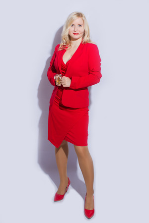 赤いスーツの美しい、セクシー、エレガントな金髪の女性モデル 写真素材