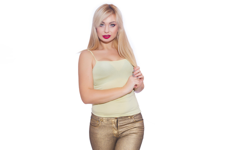 Studio portrait of a beautiful young blond woman with long hair, dressed in a summer yellow jersey and golden jeans. Foto de archivo
