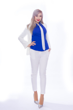 Full-length studio portrait of a business woman in a white pants suit and silver high-heeled shoes