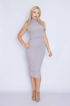 studio portrait in full growth of a young blond woman in a gray business midi-dress.