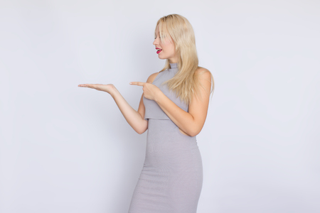 horizontal studio portrait of a young blond woman in a gray business midi-dress. Stock Photo