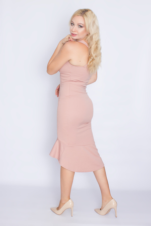 A beautiful woman in tight summer skirt with a deep neckline posing against a white background in the studio. Beige high-heeled shoes