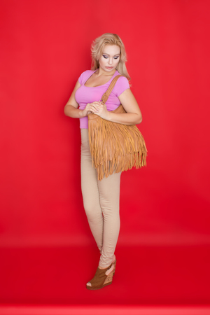 Full length portrait of fashion woman in beige jeans and with brown bag with fringe. Indoor shoot on red background. Autumn clothing concept