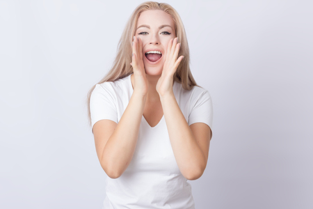 Portrait of an excited young blonde woman in white shirt screaming on grey background Stock fotó
