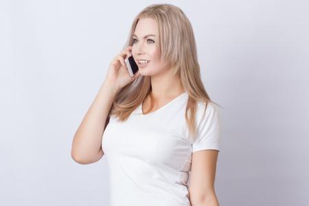 Portrait d'une belle femme blonde aux cheveux longs souriant et parlant au téléphone portable sur fond gris