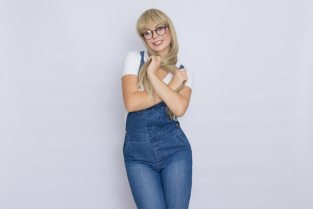 Sweet beautiful blond woman with very long hair in blue jeans overalls and glasses over grey background
