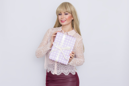 Pretty young woman with long hair is holding a packed box with a gift over white background