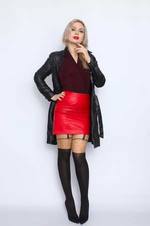 Studio portrait of a beautiful young blonde woman in a black leather coat posing on a white background in the studio