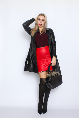 Full length portrait blonde woman in leather black coat and red leather skirt holding bag in her hands, in studio over white background