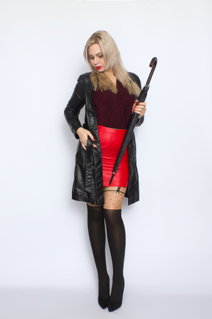 Full length portrait of blonde woman in leather black coat and red skirt holding umbrella in her hands. Over white background in studio