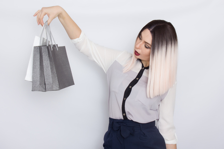 Portrait of beautiful young blonde businesswoman standing isolated over white background holding shopping bags in her hands