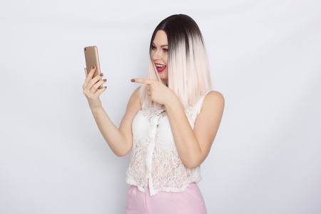 Portrait of a beautiful pensive young blonde woman standing isolated over white background , holding mobile phone Banco de Imagens