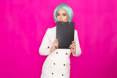 Beautiful young woman with short blue hair in a white business dress jacket holding a black folder with documents
