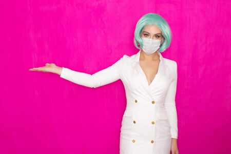 Beautiful young woman with short blue hair in a white business dress jacket with a medical mask posing on a pink background in the studio Standard-Bild