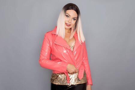 Young stylish blonde woman dressed in a golden top pink and lacquer jacket posing in the studio on a gray background