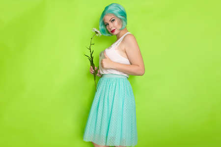 Studio portrait of beautiful mint hair feminine in white top and light blue skirt holding big chamomile in her hands, over green background