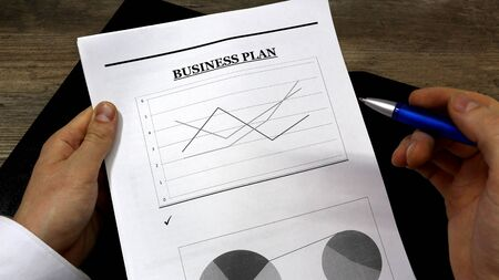 Job with finances in the office on a laptop,the employee holds paper with the inscription business plan.Businessman analyzes the chart of the rise or fall of prices and is a plan of action. businessman