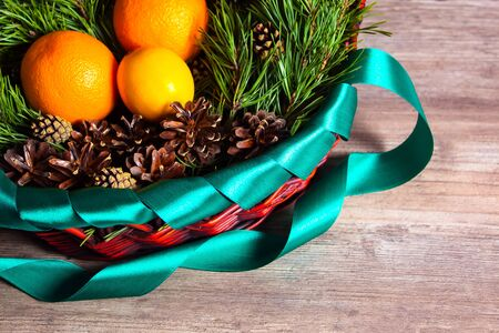 Christmas or new year  fruit basket top view. Oranges and lemon lie in a basket with a Christmas tree and Christmas cones. New year flat lay