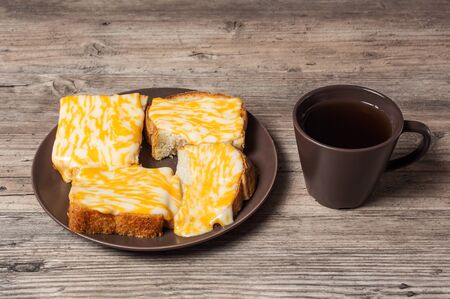 A Cup of coffee with fresh toast with melted cheese on a wooden background. Morning diet Breakfast. Proper diet. 写真素材