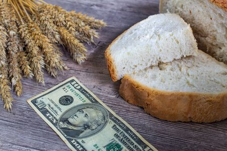 A loaf of bread and ears of ripe wheat lie on a wooden table next to US Dollars. Prices of bread and wheat in America. Exports of American wheat and flour