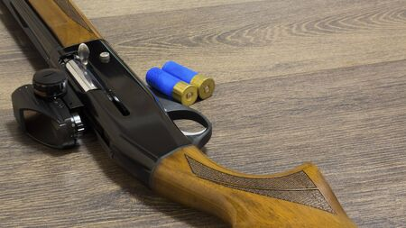 shotgun with bullets on wooden background Stock Photo