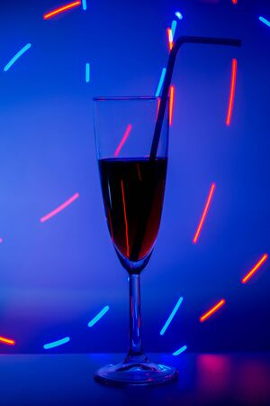 A glass on the bar in a cafe, restaurant, nightclub or disco. Glass or stemware with alcohol or a cocktail on a colored background.