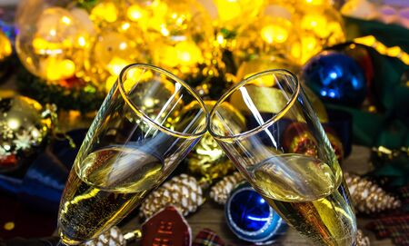 Glasses of champagne on the Christmas table with Christmas toys and garlands. New year and Christmas with glasses of champagne, holiday 2020. 写真素材