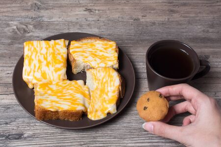 A Cup of coffee with fresh toast, melted cheese and cupcake in hand on a wooden background. Morning diet Breakfast. Proper diet.