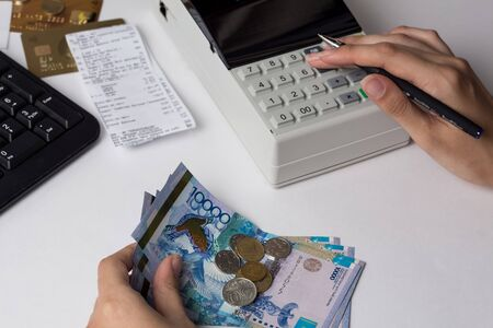 Tenge at the cashier accountant in the hands of the workplace in the office. The cashier counts the money KZT in the workplace in Kazakhstan. Salary in Kazakhstan