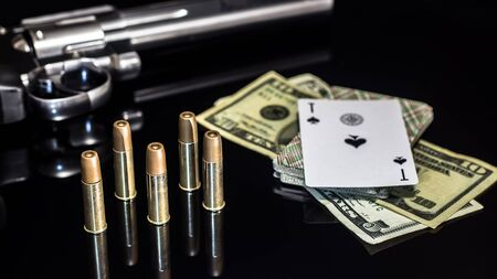 Dangerous gambling for money. A pistol with cartridges, money dollars and a deck of playing cards with an ACE of spades lie on a glass table. Dangerous gambling debts and loans.