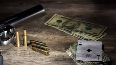 Dangerous gambling for money. A pistol with cartridges, money dollars and a deck of playing cards with an ACE of spades lie on a wooden table. Dangerous gambling debts and loans. 版權商用圖片