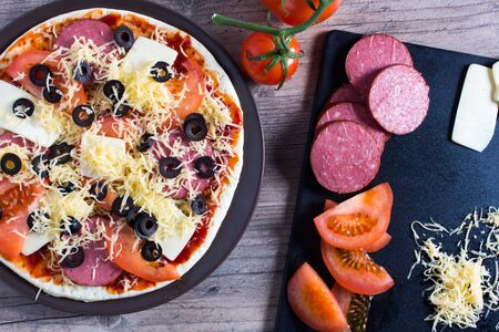 Pizza with tomatoes, olives and cheese is on the plate. Ingredients for cooking pizza are on a wooden table. Cooking pizza at home