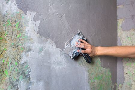 Repair the wall. Plaster the wall with a spatula. Internal construction and finishing works. The Builder puts plaster on the wall .Hand holding a spatula with construction mix and smoothes out bumps.