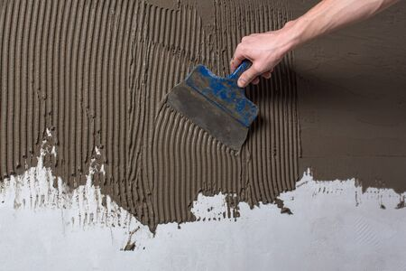 Repair the wall. Plastering the wall.Hand holding a spatula with construction mix.Applying putty or tile glue to the wall.Plaster the wall with a putty knife.Internal construction and finishing works