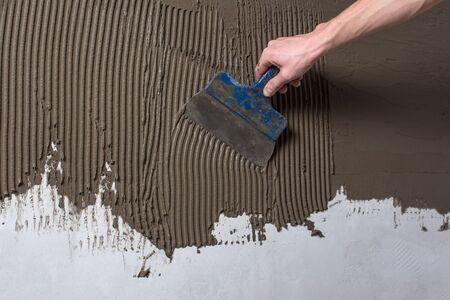 Repariere die Wand. Verputzen der Wand.Hand, die einen Spachtel mit Baumischung hält.Auftragen von Kitt oder Fliesenkleber auf die Wand.Verputzen Sie die Wand mit einem Spachtelmesser.Interne Bau- und Endarbeiten finishing