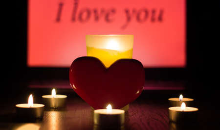 Greeting card for Valentine's day or international women's day. A red heart stands against a background of lighted candles and the inscription I love you. Christmas fortune telling and Divination fate