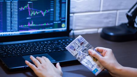Tenge in Kazakhstan against the background of a laptop with an open chart of the currency market or stock exchange. Hands holding Tenge in front of the computer. Tenge KZT, bank of Kazakhstan.