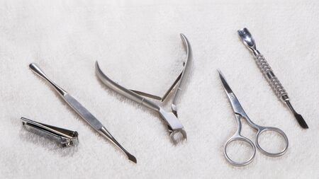 Manicure or pedicure set tools are placed on a table with a white towel in the beauty salon. Imagens
