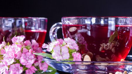 Hibiscus Red tea mug with carnation flowers close-up horizontal photo.English tea tradition.Medicinal therapy based on medicinal herbs and decoctions.Spicy herbs and medicinal broths.A relaxing drink Banco de Imagens