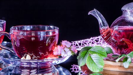 A mug of red tea and a teapot in white hibiscus flowers and green leaves of medicinal tea on a wooden stand.Zen tea ceremony. Photo of red herbal Indian healing tea.Elegant mugs with a relaxing drink