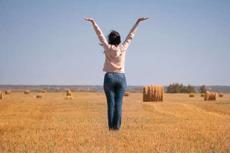 A happy, free, independent, dreamy girl in the field raised her hands to the sky. A woman in a jacket and jeans at the harvest rear view. Silhouette of a girl from behind.Harvesting of grain crops 写真素材