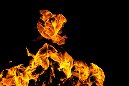 Fire flames on black background isolated. Burning gas or gasoline burns with fire and flames. Flaming burning sparks close-up, fire patterns. Infernal glow of fire in the dark with copy-space