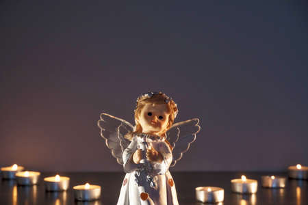 White Christmas angel with lighted candles in the Church. Spiritual deity in religion.