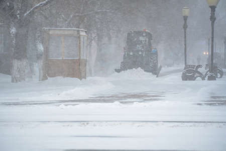 Snow removal equipment, utilities and municipal services are clearing the snow from the streets in the snow storm, Blizzard and snowstorm.Weather conditions in winter. Bad weather conditions with snow