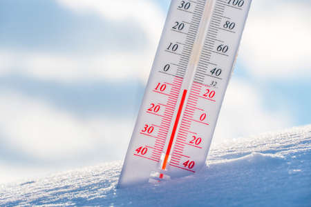 The thermometer lies on the snow in winter showing a negative temperature.Meteorological conditions in a harsh climate in winter with low air and ambient temperatures.Freeze in wintertime.Sunny winter Stock Photo