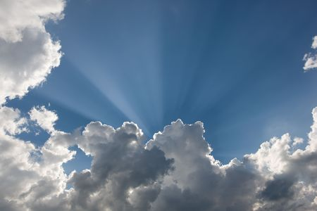 Beatiful sun rays in blue sky, downy clouds
