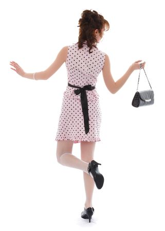 A young fashionable young woman dressed in a trendy, glamorous outfit.  White background.