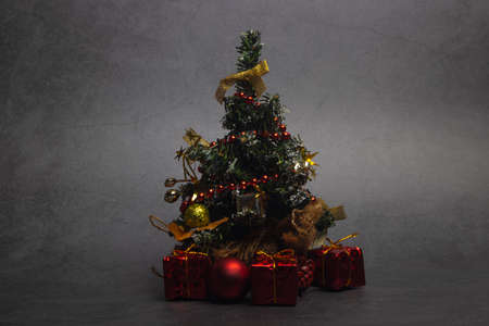 Small Christmas tree with presents and New Year's red decorations on a dark background.