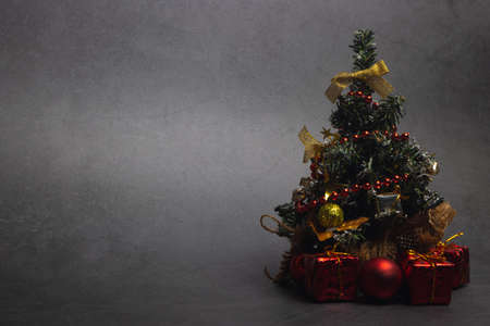 Small Christmas tree with presents and New Year's red decorations on a dark background. Copy space