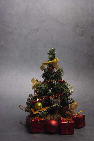Small Christmas tree with presents and New Year's red decorations on a dark background. Vertical orientation